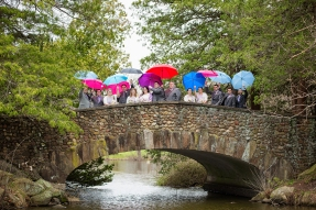 Not disheartened by the rain, the bridal party use colored umbrellas that their photographer brought along in order to create a beautiful photograph on the stone bridge in West Hartford Connecticut.