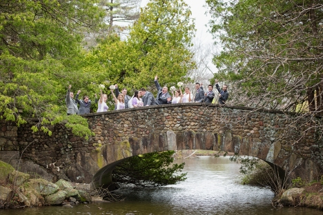 The bridal party cheers as the bride and groom kiss along the stone bridge of Elizabeth Park in West Hartford Connecticut