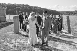 The bride and groom, followed by their bridal party, walk along the docks during their Mystic Seaport Connecticut Wedding.