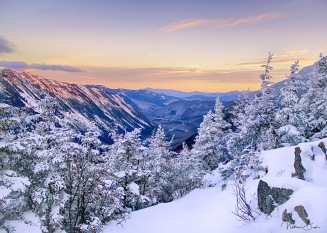 The sun sets to the west, just beyond the mountain ridgetops of the White Mountains, leaving a beautiful orange tint in the sky and reflecting across the snow-covered mountain ridge to the left of the image. In the foreground, snow-covered trees stand still in the cold winter evening.