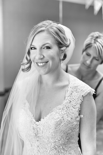 An absolutely gorgeous portrait of the bride getting fitted into her gown before her wedding day at Mystic Seaport, Mystic CT.