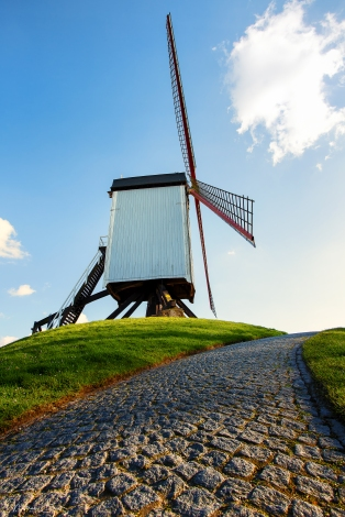 The Bonne Chiere windmill, originally constructed in 1844 and reconsturcted in 1911 after the original was blown down in a storm in 1903, stands perched on a grass hill in Bruges Belgium. A cobblestone walkway in the foregrounds acts as a leading line to lead your eyes to the windmill, outlined by the soft blue sky and puffy white clouds.
