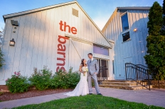 The bride and groom pose in front of the barn doors at the Barns at Wesleyan Hills Venue in Middletown Connecticut. The setting summer sun illuminates the barn in soft light during this beautiful Fall evening wedding.