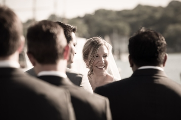 Framed by the groomsmen's suits, this candid photograph of the bride during her wedding ceremony in Mystic Connecticut is absolutely stunning.