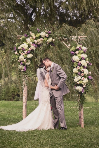 The bride and groom's first kiss under a beautiful archway built by the bride herself during the Barns at Wesleyan Hills wedding.