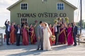 Ashley and Upamanyu kiss in front of the classic Thomas Oyster CO building as their bridal party cheers during their Mystic Seaport Wedding