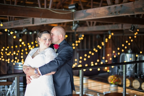 The bride and groom embracing in the balcony overlooking the winery at SaltWater Vineyards, Stonington CT