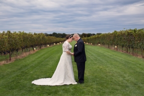 An overcast sky created a perfect texture for this landscape-like photograph of the bride and groom during their wedding at Saltwater Vineyards