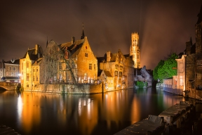 During an evening rainstorm, buildings including the Belfry in Brugge Belgium are illuminated by city lights and reflect in the canal in the foreground of the image.