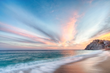 As the water recedes back into the pacific, the sun sets over the beach of Cabo San Lucas, lighting the sky in fiery orange and reflecting orange light off of the teal blue water in the foreground.