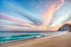 The sun sets over the pacific ocean as a teal blue wave crashes on the beach in Cabo San Lucas Mexico. Whispy clouds ignite into brilliant orange color that reflects off of the teal water's surface.