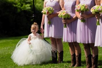 The cute flower girl sports her poofy dress as she holds her mother's hand during the ceremony at this Middletown CT Wedding.