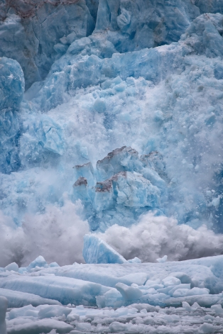 Sawyer Glacier in Tracy Arm Fjord, Juneau Alaska, calving. Huge peices of ice break away and form and iceberg.