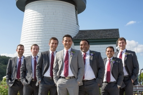 The groom and groomsmen pose in front of a lighthouse at Mystic Seaport in Mystic Connecticut.