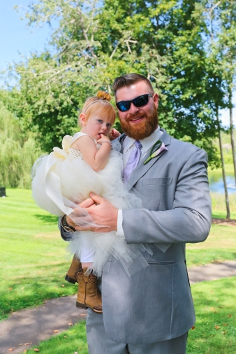 This father, a member of the groomsmen, holds his daughter, the flower girl, proudly in his arms for this portrait photograph of the two of them.