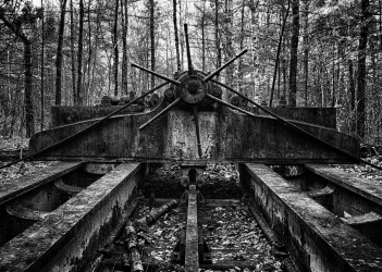 """""""Hard Work Past"""" is a black and white photograph of old machinery long forgotten in the woods at abandoned Redstone Quarry in New Hampshire. It seems to resonate hard work from the past when this Quarry was up and running as straight steel beams act as the foreground to the image and lead the viewer's eyes right to an old iron wheel in the center of the image. This photograph is presented in black and white to bring out the texture in the rust of the iron machinery and the contrast between the machinery and the trees of the forest in the background."""