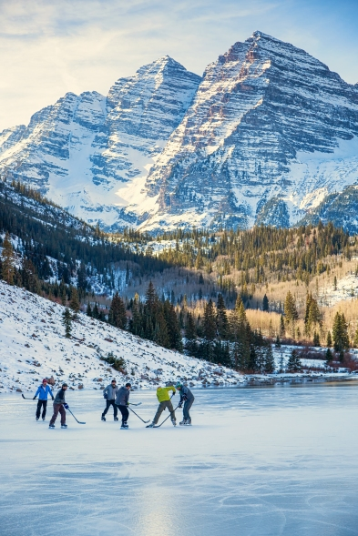 For the first time in 40 years, it is cold enough for Maroon lake to freeze over, but dry enough that there is no snow covering the ice, allowing these hockey players to play a match on this beautiful alpine lake with famous Maroon Bells towering in the background.