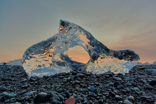 An arch of ice resting on the beach in Iceland beautifully reflects the orange color of the sunrise at Jökusárlón Glacier Lagoon, Iceland.