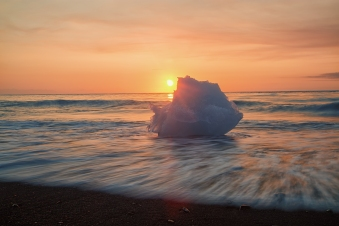 A chunck of Ice from an Iceberg at the Jökusárlón Iceberg Lagoon in Iceland washed up ashore as the sun rises behind it and the colors of the sunrise reflect in the motion of the water in the foreground.