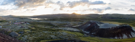 A Panoramic landscape view of the sun setting over the Icelandic landscape as seen from the summit of Grabrok crater.