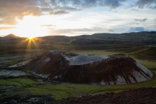 The last sun rays kiss a volcanic crater in Iceland as the sun falls over the horizon in the distance.