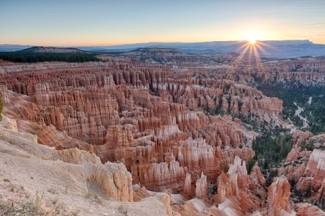 The summer solstice sun rises just above a plateau in the distance, casting warm summer rays of light among the hoodoos in the canyon of Inspiration Point, Bryce Canyon National Park.