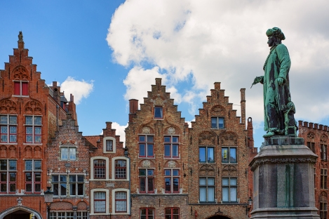 """""""As Eyck Can"""" - The motto of Flemish/Netherlandish painter Jan Van Eyck who is renown for his works while living in Bruges Belgium. Here, is statue stands in Jan Van Eyck Square with paintbrush in hand, the photographic composition as if he is painting the medieval rooftops in the background."""