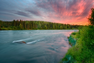 A fine-art landscape photograph of the sun setting in vibrant orange pink and purple clouds as the teal color of the Kenai River flows past the lush green river banks on the side.