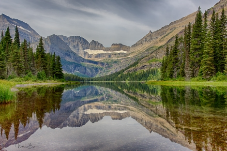 The surrounding mountain peaks along the Grinnell Glacier trail reflect in the crystal clear water of Lake Josephine in Glacier National Park.