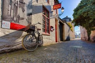 "An interesting bicycle with the word ""LUX"" inscribed on its basket rests against and old brewery along a cobblestone walkway in local Bruges, Belgium."