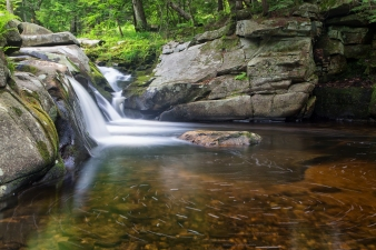 A serene circle of flowing bubbles makes for the perfect foreground over the orange rocks under the water, with Mad River Falls flowing gracefully over the rocks in the background of this image from Farmington New Hampshire.