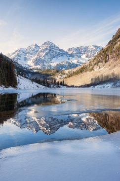 This beautiful rare photograph depicts partially frozen Maroon Lake in the foreground with the edge of the ice acting as a leading line to draw your eye past the beautiful reflection to the gorgeous Maroon Bells mountain Peaks in the background.