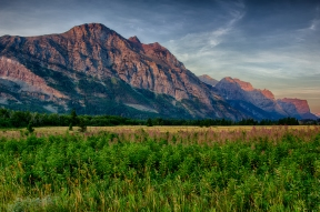 The first rays of sunrise light touch the mountainside in the early morning at Glacier National Park.