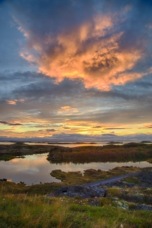 The sun sets and reflects intense orange light into the clouds over lake Myvatn, Iceland.