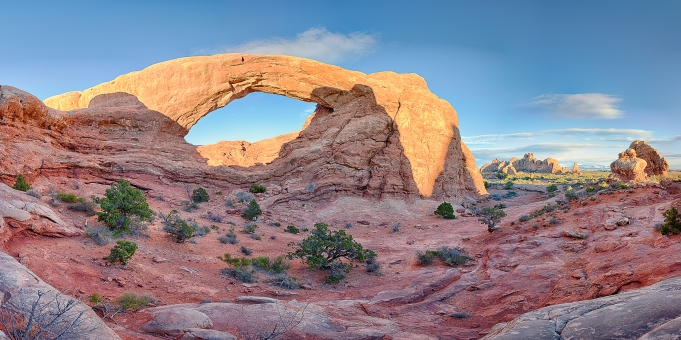 The setting sun casts warm orange light on South Window Arch during sunset at Arches National Park. This panoramic photo captures the expanse of Arches National Park beautifully.