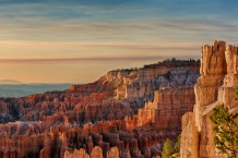 As the sun crests above the horizon, Inspiration Point and the surrounding canyon is painted in orange light at Bryce Canyon National Park.