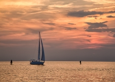 The sun sets behind a sailboat returning to harbor in the foreground on the North Carolina outer Banks.