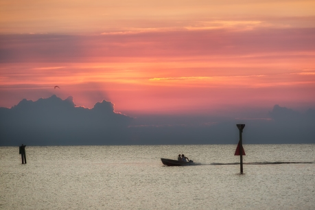 Two boaters cruise toward across the water in a small motorized rowboat off the coast of the Outer Banks, NC, with a beautiful orange and pink sunset behind them.