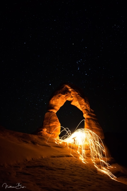 Photographed at night under the constellation Orion in the background-- steel wool sends bright sparks flying into the night at Delicate Arch in Arches National Park.