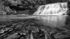 A beautiful black and white photograph of Wadsworth Falls at Wadsworth Falls State Park in Connecticut. In the foreground of this photograph, small stones protrude slightly from the water's surface and natural bubbles in the water creating curving lines that draw the viewers eyes directly to the waterfall in the background.