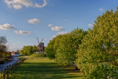 A park in Bruges, Belgium is the home of two old windmills. Here, one of the old mills stands atop a grassy knoll looking toward the sun. The parks tree line a canal to the right.